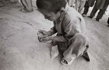 Peshawer, Pakistan -- An Afghan refugee child picks up lentils that have been spilled during distribution in Shamshatoo refugee camp. Food aid is distributed only once a month by the World Food Program in each refugee camp in Pakistan. The aid each refugee receives is limited to 15 kgs. of flour, 1 kg lentils, 0.75 lt. vegetable oil a month. 10/13/01 Photo by Bikem Ekberzade.